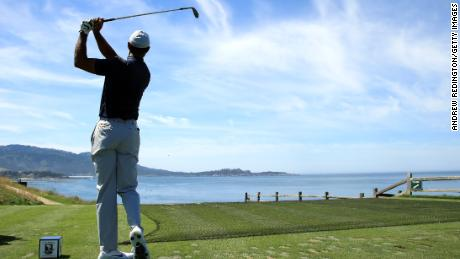 Tiger Woods tees off on the iconic short seventh hole at Pebble Beach.