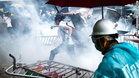 Protesters run after police fired tear gas outside government headquarters on June 12.