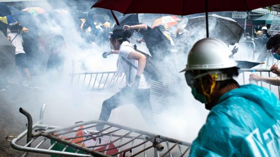 Protesters run after police fired tear gas on Wednesday, June 12.
