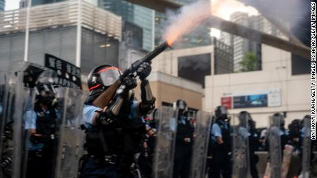 HONG KONG, HONG KONG - JUNE 12:  A police officer fire teargas during a protest on June 12, 2019 in Hong Kong China. Large crowds of protesters gathered in central Hong Kong as the city braced for another mass rally in a show of strength against the government over a divisive plan to allow extraditions to China. (Photo by Anthony Kwan/Getty Images)