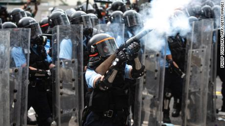 A policeman kicks tear gas during conflicts with protesters during a rally against a controversial extradition proposal outside the government headquarters in Hong Kong on June 12, 2019. A policeman kicks tear gas during conflicts with protesters during a rally against a controversial extradition bill outside the government headquarters in Hong Kong on June 12, 2019.