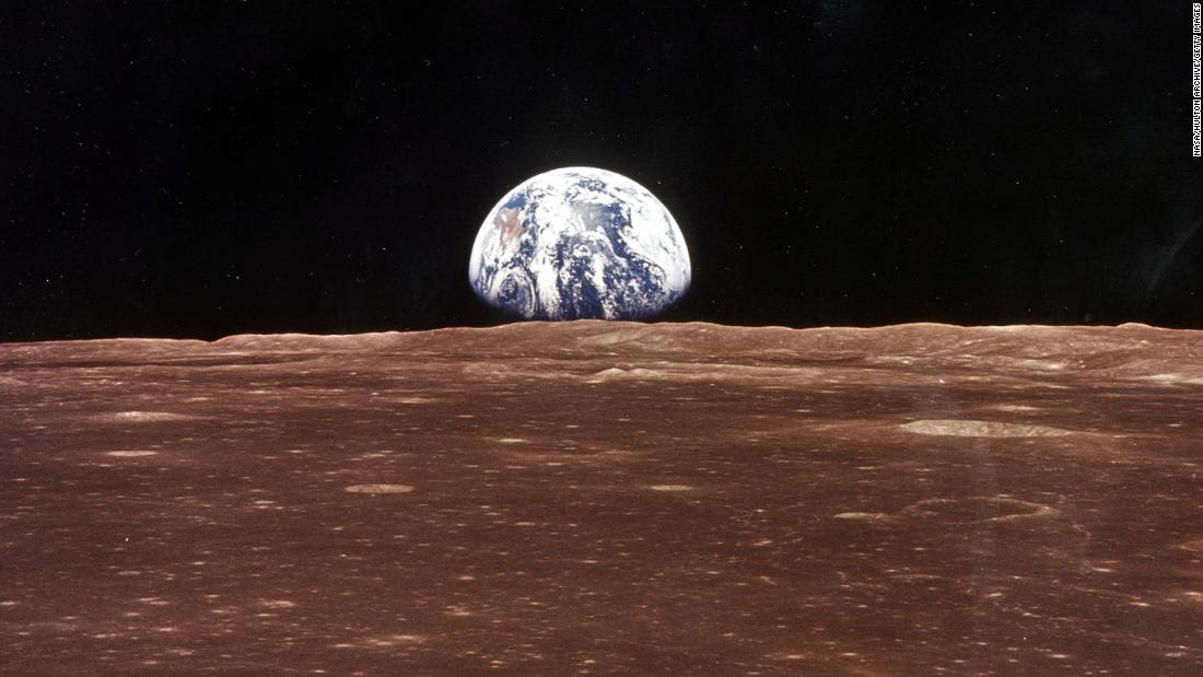 A view of Earth appears over the lunar horizon as Apollo 11's command module comes into view of the moon.