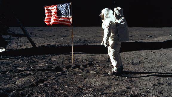 376713 03: (FILE PHOTO) Astronaut Edwin E. Aldrin, Jr., the lunar module pilot of the first lunar landing mission, stands next to a United States flag July 20, 1969 during an Apollo 11 Extravehicular Activity (EVA) on the surface of the Moon. The 30th anniversary of Apollo
