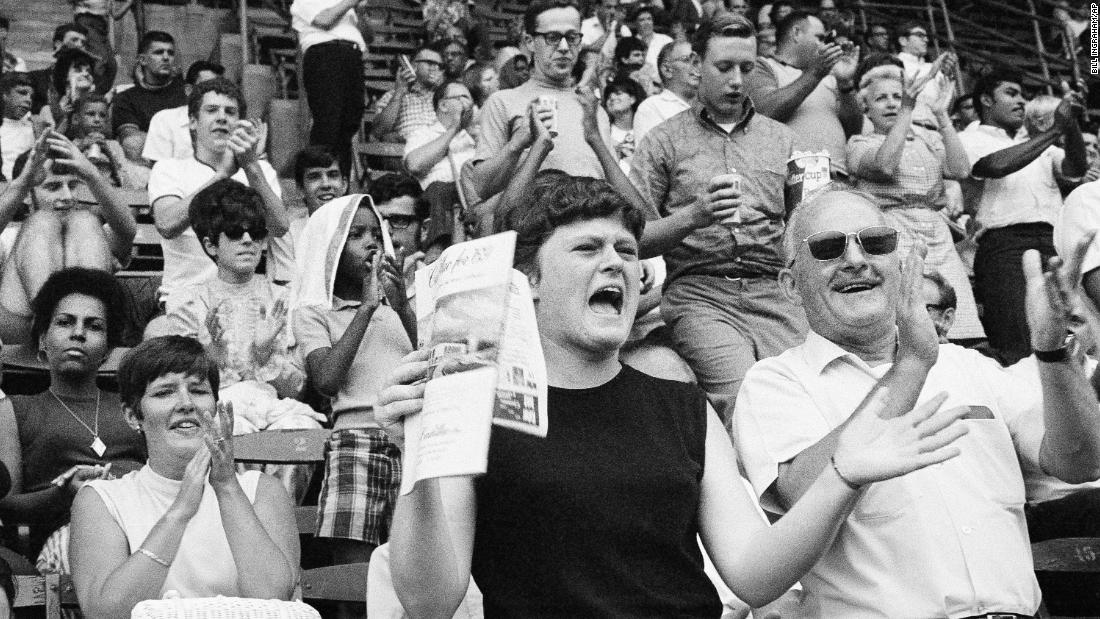 Fans attending a Philadelphia Phillies baseball game cheer after it was announced that the Eagle had made a safe lunar landing on July 20, 1969.