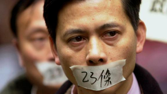 """A demonstrator  put tape over his mouth with the words """"Article 23"""" written on it in 2003."""