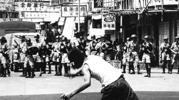 A rioter hurls rocks at riot police patrol during riots in Hong Kong, May 1967.