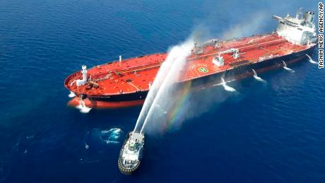An Iranian navy boat sprays water to extinguish a fire on an oil tanker in the sea of Oman, Thursday, June 13, 2019. Two oil tankers near the strategic Strait of Hormuz came under a suspected attack Thursday.
