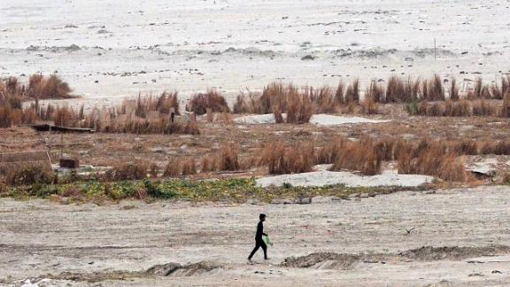 A man crosses the dried river bed of the shrunken Ganges in Allahabad on June 12.