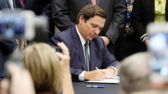 Florida Gov. Ron DeSantis signs the Sanctuary City bill Friday, June 14, 2019 at the Okaloosa County, Fla., Commission Chambers in Shalimar Fla. The bill requires all law enforcement agencies in Florida to cooperate with federal immigration authorities.