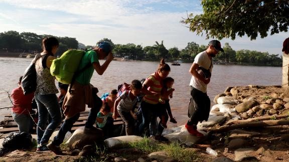 """Migrants and residents use a makeshift raft to illegally cross the Suchiate river, from Tecun Uman, in Guatemala to Ciudad Hidalgo, Chiapas state, Mexico on June 14, 2019. - Mexico's Foreign Minister Marcelo Ebrard said Mexico will discuss a """"safe third country"""" agreement with the US -- in which migrants entering Mexican territory must apply for asylum there rather than in the US -- if the flow of undocumented immigrants continues. (Photo by QUETZALLI BLANCO / AFP)        (Photo credit should read QUETZALLI BLANCO/AFP/Getty Images)"""