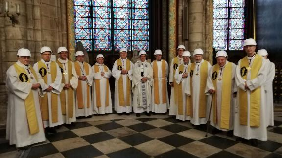 Michel Aupetit, the Archbishop of Paris (center), poses with other members of the clergy following the Mass.