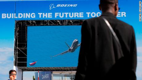 Visitors walk past a giant screen of Boeing as as the lading of a 737 Max is shown at Paris Air Show, in Le Bourget, east of Paris, France, Monday, June 17, 2019. The world's aviation elite are gathering at the Paris Air Show with safety concerns on many minds after two crashes of the popular Boeing 737 Max. (AP Photo/Michel Euler)