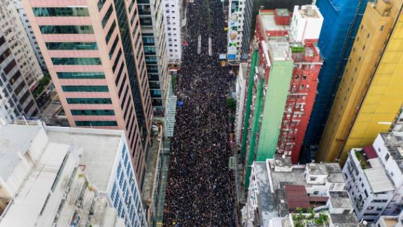 TOPSHOT - This overhead view shows thousands of protesters marching through the street as they take part in a new rally against a controversial extradition law proposal in Hong Kong on June 16, 2019. - Tens of thousands of people rallied in central Hong Kong on June 16 as public anger seethed following unprecedented clashes between protesters and police over an extradition law, despite a climbdown by the city
