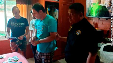 Italian Francesco Galdelli, center, is arrested by Thai police officers at a house in Chonburi.