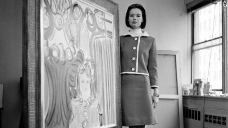 Wearing a red Courreges suit piped with white leather, Gloria Vanderbilt Cooper poses with one of her paintings, at her private studio in New York City,  April 5, 1966.  (AP Photo)