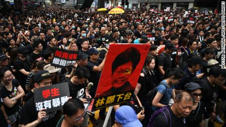 TOPSHOT - A placard (C) with an image of Hong Kong's Chief Executive Carrie Lam is displayed as thousands of protesters dressed in black take part in a new rally against a controversial extradition law proposal in Hong Kong on June 16, 2019. - Tens of thousands of people rallied in central Hong Kong on June 16 as public anger seethed following unprecedented clashes between protesters and police over an extradition law, despite a climbdown by the city's embattled leader. (Photo by HECTOR RETAMAL / AFP)        (Photo credit should read HECTOR RETAMAL/AFP/Getty Images)