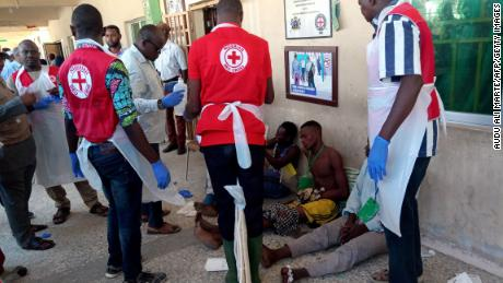 EDITORS NOTE: Graphic content / Red Cross officials attend to victims of a triple suicide bombing, which occured outside a hall in Konduga, 38 kilometres (24 miles) from the Borno state capital Maiduguri, northeast Nigeria, on June 17, 2019. - Thirty people were killed late on June 16 in a triple suicide bombing in northeast Nigeria, emergency services reported, in an attack bearing the hallmarks of the Boko Haram jihadist group. Three bombers detonated their explosives outside a hall in Konduga, 38 kilometres (24 miles) from the Borno state capital Maiduguri, where football fans were watching a match on TV. (Photo by Audu Ali MARTE / AFP)        (Photo credit should read AUDU ALI MARTE/AFP/Getty Images)