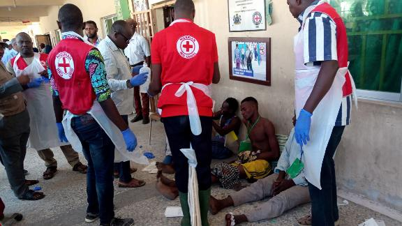 EDITORS NOTE: Graphic content / Red Cross officials attend to some victims injured in the Konduga bombings on Monday.