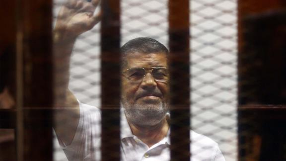 CAIRO, EGYPT - JULY 07: Mohamed Morsi waves as he stands inside a glass defendant's cage during his trial in Cairo, Egypt, on July 07, 2014. An Egyptian court on Monday adjourned to July 13 the trial of Mohamed Morsi and 130 others charged with breaking out of jail in 2011, a judicial source has said. Judges postponed the trial proceedings in order to hear the accounts of more witnesses, the source added. (Photo by Stringer/Anadolu Agency/Getty Images)