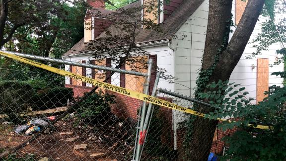 Police tape surrounds the house where Askia Khafra died in a fire while digging tunnels.