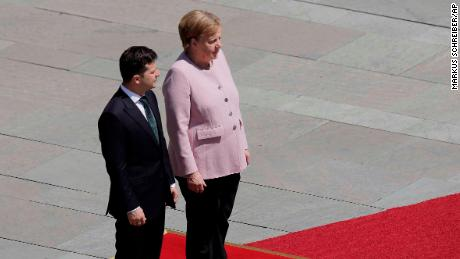 German Chancellor Angela Merkel stands next to Ukraine's President Volodymyr Zelenskiy during military honors for a meeting at the chancellery in Berlin, Germany, Tuesday, June 18, 2019. (AP Photo/Markus Schreiber)