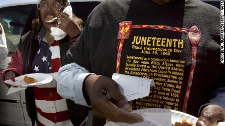 Naomi Williams, left, and D'Emanuel Grosse Sr. taste the sweet potato pie entered in the cook-off contest at the Juneteenth Black Independence Day celebrations in Richmond, California on Wednesday.