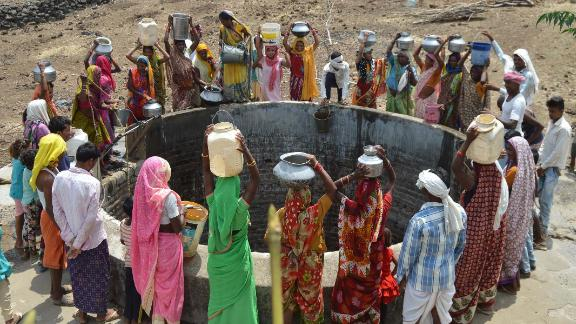 Indian women from the aboriginal 'Kol' community collect drinking water at a well in Nawargawa village, some 30km from Jabalpur, in Madhya Pradesh state on June 16.