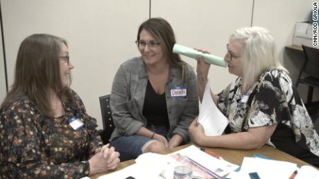 Peggy Oyer (right) participates in a listening exercise that illustrates how anyone who hears voices while experiencing a psychotic episode may feel.