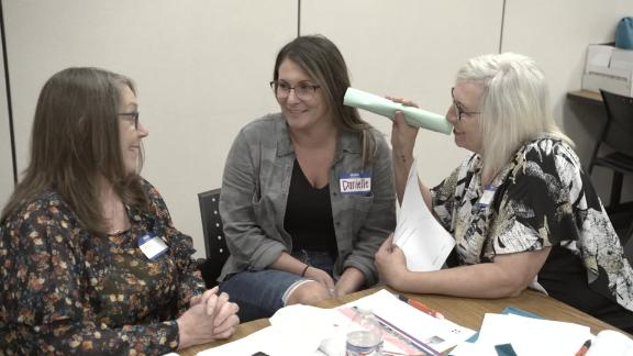 Peggy Oyer (right) takes part in a listening exercise that illustrates how someone hearing voices while experiencing a psychotic episode might feel.