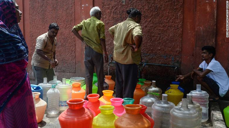 Indian residents stand around with plastic pots filled with drinking water at a distribution point in Chennai on June 19, 2019.