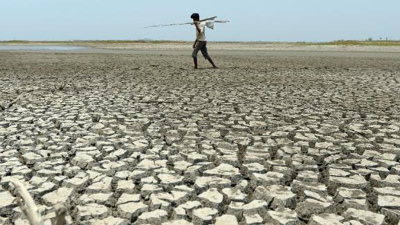 An Indian man walks over the parched bed of a reservoir on the outskirts of Chennai on May 17, 2017