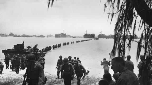 Army reinforcements wade ashore on Saipan without enemy opposition. They relieved Marines in the battle of attrition raging in the island's interior. The ships of Task Force 58 are behind them in the Pacific Ocean.