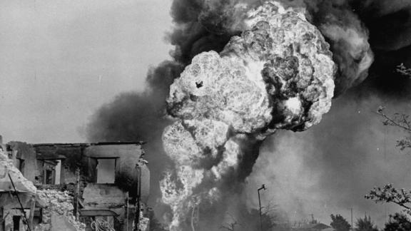 Smoke and flames pour from ruins of buildings hit during a fierce battle to take Saipan from occupying Japanese forces.