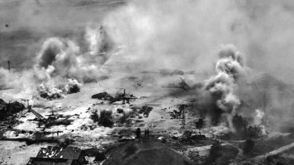 Smoke rises into the sky from the US artillery and naval bombardment of a Japanese seaplane base at Flores Point, near Tanapag Harbor.