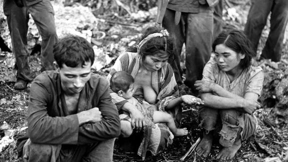 A civilian family squats on the ground, surrounded by US Marines after the battle between US and Japanese forces for control of Saipan in July 1944.