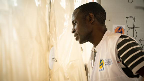 Dr. Camara Modet of Alima, a French medical non-governmental organization, looks in on his Ebola patient through the walls of the CUBE. It