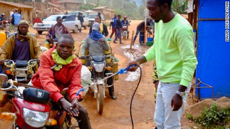A motorcycle taxi driver gets his hands washed with a chlorine solution at a checkpoint between Beni and Butembo in eastern Democratic Republic of Congo. Temperatures are therefore checked and possible Ebola isolated. Still, many Ebola victims have traveled north and Kivu and Ituri provinces.