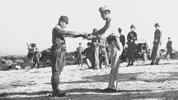 Imperial Japanese Army Capt. Sakae Oba surrenders his sword to Lt. Col. Howard C. Kurgis.