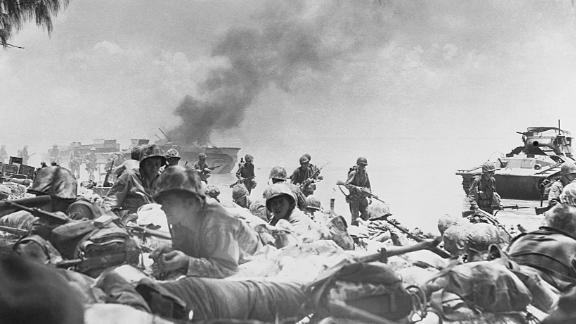 US Marines crawl on the beach to avoid Japanese gunfire after landing on Saipan.
