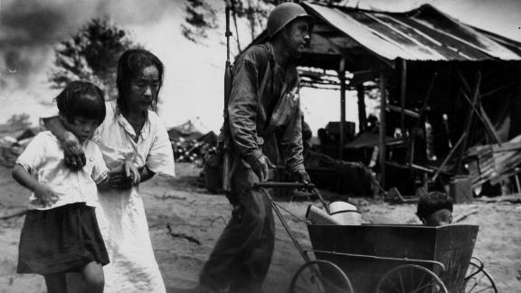 A US soldier pushes a baby carriage while escorting a family to an internment camp during the Battle of Saipan.