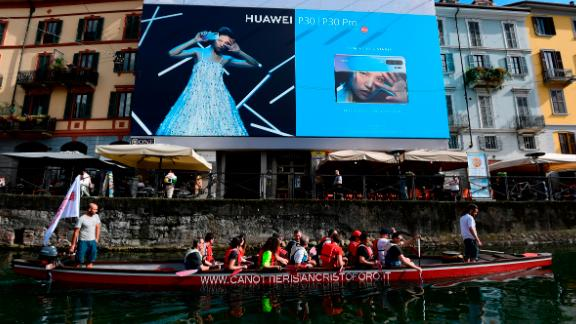 Tourists on a boat pass by a Huawei billboard on the Naviglio canal, south of Milan.