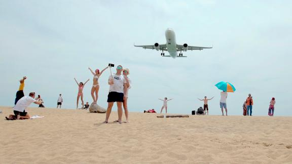 Tourists pose for photographs as an airplane descends into Phuket International Airport.