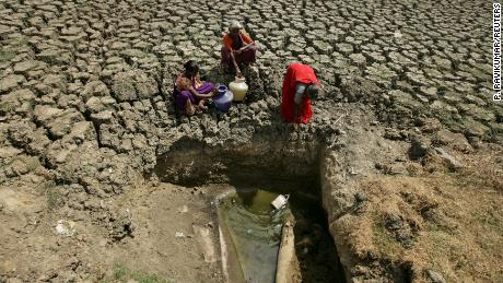 FILE PHOTO: Women fetch water from an opening made by residents at a dried-up lake in Chennai, India, June 11, 2019. REUTERS/P. Ravikumar/File Photo