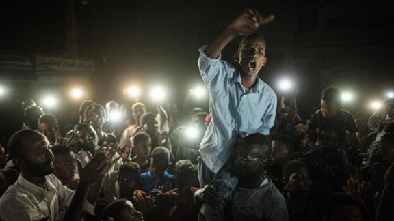 People chant slogans as a young man recites a poem, illuminated by mobile phones, before the opposition