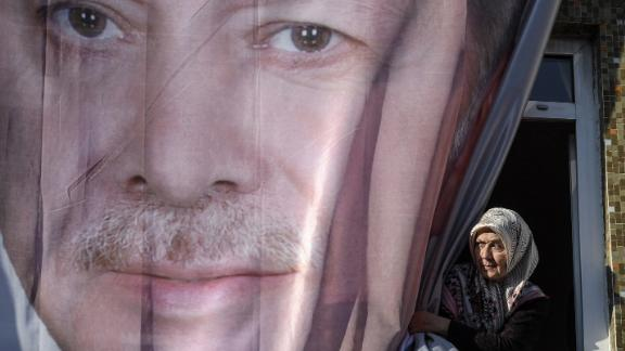 A woman peers out from behind a giant poster of Erdoğan during a March rally in Kasımpaşa.