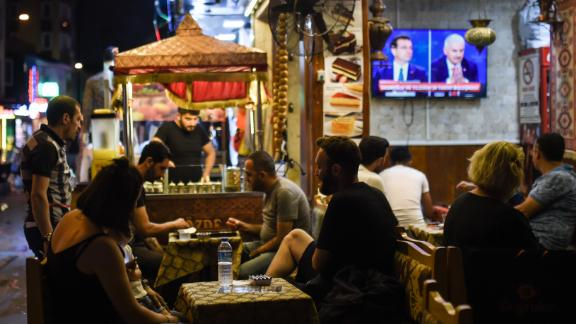 At an Istanbul café, people watch a live TV debate between Istanbul's main mayoral candidates.