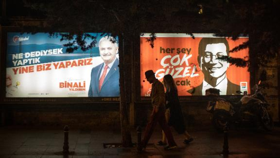 People walk past Yıldırım and İmamoğlu election posters amid campaigning for the rerun.
