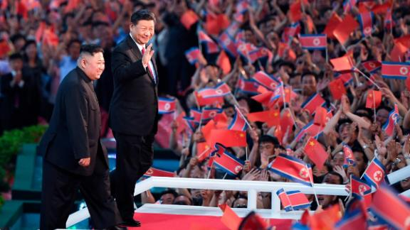 Spectators wave Chinese and North Korean flags as North Korean leader Kim Jong Un, left, and visiting Chinese President Xi Jinping attend a mass gymnastic performance at the May Day Stadium in Pyongyang, North Korea.