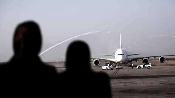 Iranian women watch an Airbus A380-800 airctaft of Emirates Airline being given a water cannon salute after landing at Tehran's IKA airport on September 30, 2014. Dubai's Emirates Airline made a one-off flight to the Iranian capital for the first time with its flagship Airbus A380 plane to celebrate its recent introduction of more flights on the route. AFP PHOTO/BEHROUZ MEHRI        (Photo credit should read BEHROUZ MEHRI/AFP/Getty Images)