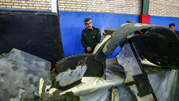 Gen. Amir Ali Hajizadeh, Iran's head of the Revolutionary Guard's aerospace division, looks at debris from a downed US drone on June 21, 2019.